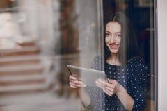 La chica joven hermosa goza del teléfono y de la tableta Foto de archivo
