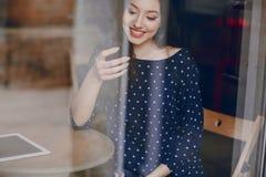 La chica joven hermosa goza del teléfono y de la tableta Foto de archivo libre de regalías