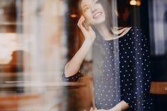 La chica joven hermosa goza del teléfono y de la tableta Imágenes de archivo libres de regalías