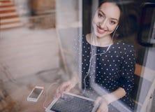 La chica joven hermosa goza del teléfono y de la tableta Imagenes de archivo