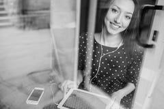 La chica joven hermosa goza del teléfono y de la tableta Fotografía de archivo libre de regalías