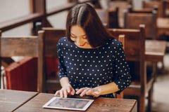 La chica joven hermosa goza del teléfono y de la tableta Imagen de archivo libre de regalías