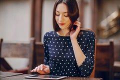 La chica joven hermosa goza del teléfono y de la tableta Imagen de archivo