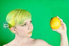 La chica joven hermosa mira el limón en fondo verde Fotos de archivo