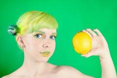 La chica joven hermosa mira el limón en fondo verde Imágenes de archivo libres de regalías