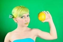 La chica joven hermosa mira el limón en fondo verde Foto de archivo libre de regalías