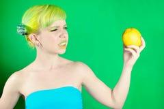 La chica joven hermosa mira el limón y estropea la cara en fondo verde Fotos de archivo