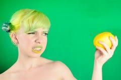 La chica joven hermosa mira el limón y estropea la cara en fondo verde Imagen de archivo libre de regalías