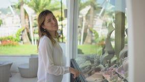 La chica joven hermosa mira en la cámara y pide que un individuo compre una joyería en ventana de la tienda durante compras almacen de video