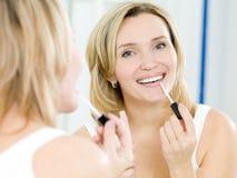 La chica joven hermosa pone un lustre del labio Foto de archivo libre de regalías