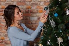La chica joven hermosa que adorna un árbol de navidad juega Días de fiesta, regalo, y concepto del Año Nuevo Foto de archivo