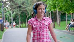 La chica joven hermosa que escucha la música en los auriculares azules patina en el parque metrajes