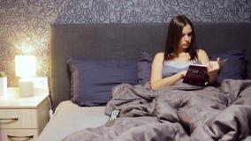 La chica joven hermosa que mentía en la cama en el dormitorio, leyó un libro culinario Mujer que descansa por la tarde en casa almacen de video