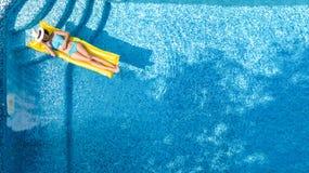 La chica joven hermosa que se relaja en la piscina, nadadas en el colchón inflable y se divierte en agua el vacaciones de familia fotos de archivo libres de regalías