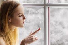 La chica joven hermosa que se sienta por el día de invierno de la ventana y dibuja el sol en la ventana congelada Imágenes de archivo libres de regalías