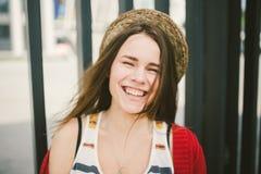 La chica joven hermosa que sonríe, es feliz, feliz en un sombrero, una camisa roja sobre ciudad Fotografía de archivo