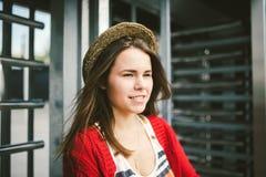 La chica joven hermosa que sonríe, es feliz, feliz en un sombrero, una camisa roja sobre ciudad Fotos de archivo libres de regalías
