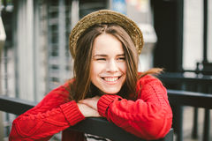La chica joven hermosa que sonríe, es feliz, feliz en un sombrero, una camisa roja sobre ciudad Imagen de archivo libre de regalías