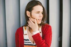 La chica joven hermosa que sonríe, es feliz, feliz una camisa roja sobre ciudad Imagen de archivo