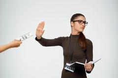 La chica joven hermosa rechaza sobre el dinero que mira a un lado Sobre el fondo blanco Foto de archivo