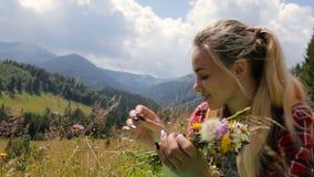 La chica joven hermosa recoge las flores salvajes en las montañas almacen de video