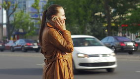 La chica joven hermosa se coloca en un fondo del tráfico urbano, tiro medio almacen de metraje de vídeo