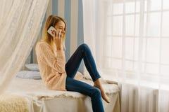 La chica joven hermosa se está sentando en la cama mientras que habla en el teléfono móvil en el dormitorio Fotos de archivo libres de regalías
