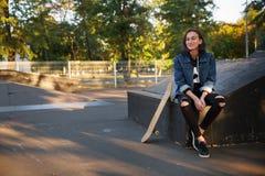 La chica joven hermosa se sienta al aire libre con un monopatín Fotos de archivo libres de regalías