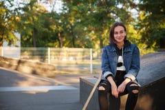 La chica joven hermosa se sienta al aire libre con un monopatín Fotografía de archivo