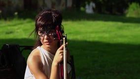 La chica joven hermosa se sienta en un banco con un violín en parque hermoso almacen de metraje de vídeo