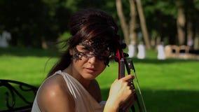 La chica joven hermosa se sienta en un banco con un violín en parque hermoso almacen de video