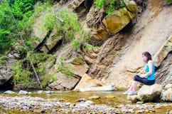 La chica joven hermosa se sienta en una roca en el río Fotos de archivo