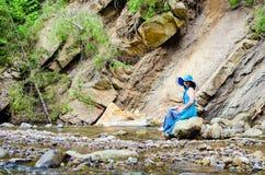 La chica joven hermosa se sienta en una roca en el río Fotografía de archivo libre de regalías