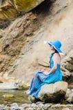La chica joven hermosa se sienta en una roca en el río Fotos de archivo libres de regalías