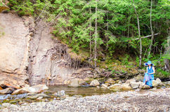 La chica joven hermosa se sienta en una roca en el río Foto de archivo libre de regalías