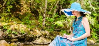 La chica joven hermosa se sienta en una roca en el río Imagen de archivo libre de regalías