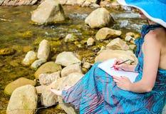 La chica joven hermosa se sienta en una roca en el río Fotografía de archivo