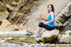 La chica joven hermosa se sienta en una roca en el río Imagen de archivo