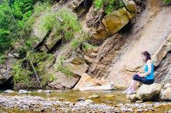 La chica joven hermosa se sienta en una roca en el río Imagenes de archivo