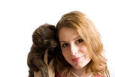 La chica joven hermosa sonriente con su bebé persigue el animal doméstico fotografía de archivo