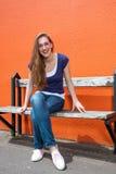 La chica joven hermosa sonriente que se sienta en una universidad soleada bench Foto de archivo libre de regalías
