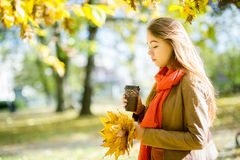 La chica joven hermosa tiene café en el parque del otoño Imágenes de archivo libres de regalías