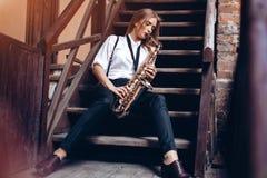 La chica joven hermosa toca un saxofón que se sienta en pasos - al aire libre La mujer atractiva en la expresión blanca de la cam Foto de archivo