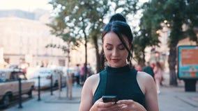La chica joven hermosa utiliza su teléfono móvil mientras que camina abajo de la calle de la ciudad, frota ligeramente su pelo, t metrajes