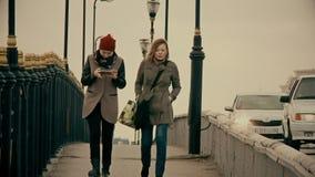 La chica joven hermosa utiliza un smartphone en un puente de la ciudad, Kazajistán, Atyrau metrajes