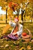 La chica joven lanza un ramo de hojas de otoño fotos de archivo