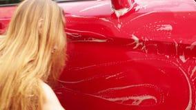 La chica joven lava un coche rojo metrajes