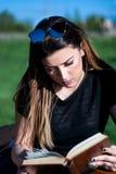 La chica joven lee el libro cuidadosamente en día de primavera soleado en el parque en un banco Foto de archivo libre de regalías