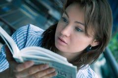 La chica joven lee el libro interesante Imagen de archivo