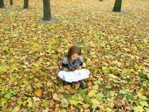 La chica joven lee un libro en el parque del otoño Fotografía de archivo